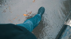 A man walks under an umbrella through a puddle in the rain. Slow mo, slo mo Stock Footage