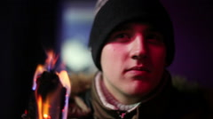 Young man in jacket and hat holding a torch andlooking somewhere - stock footage