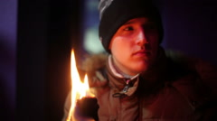 Young man in jacket and hat holding a torch andlooking somewhere Stock Footage