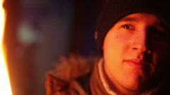 The young man in winter clothes in the light of the fire looking at the camera - stock footage