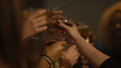 4K Happy party crowd raise their glasses for a toast, celebration in city bar Stock Footage