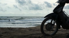 Silhouette of motorcycle parked at beach, woman enjoying the waves - stock footage