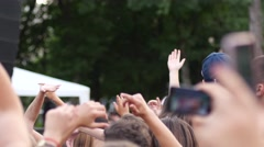 Crowd people spectators young fans open air concert raise wave hands up in air Stock Footage