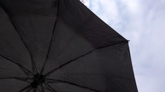 Closing the black automatic umbrella on cloud background when rain stops Stock Footage
