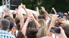 Cheering people crowd fan spectators jump wave hands enjoy open air concert Stock Footage