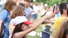 Cute little girl fan spectator in a crowd people shooting video via smart phone Stock Footage