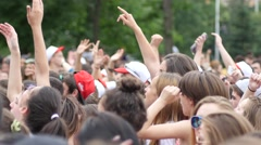 Spectators people crowd waving hands above heads enjoying jump by concert stage - stock footage