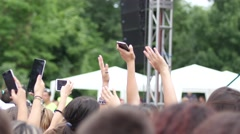 Spectators waving hands hold smart phone shooting video of open air concert fest Stock Footage