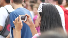 Spectator girl hold smart phone shooting video of open air concert festival Stock Footage