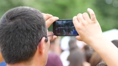 Man hold smart phone shooting video of open air concert festival Stock Footage