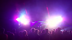 Crowd of people illuminated by colorful light during a concert - stock footage