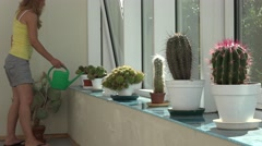 Gardener florist woman watering cactus plant with green watering can in Stock Footage