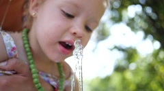 Little child girl funny catch water jet with mouth drink from drinking fountain - stock footage