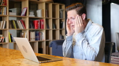 stressed businessman sitting in his office using laptop - stock footage