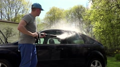 Man, hosing his car at do it yourself car wash, using high pressure water spray Stock Footage