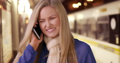 Beautiful young woman tells her friend on cell phone that the train is picking Stock Footage