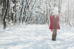 Woman with a red coat is hiding her face, snowy forest in winter Stock Photos