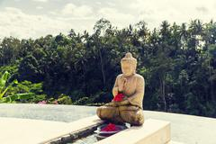 infinity edge pool with buddha statue - stock photo
