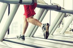 Close up of male legs running on treadmill in gym Stock Photos