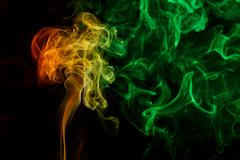Abstract yellow green smoke from aromatic sticks. - stock photo