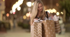 Young sexy material girl looking through paper bags after latenight shopping Stock Footage