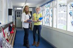 Two female teachers standing in the school corridor. They are holding school - stock photo