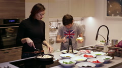 Woman and Teenager Boy Preparing Food on Kitchen Stock Footage