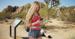 Beautiful woman navigating through Joshua Tree National Park using mobile device - stock footage