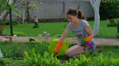 Young girl planting flowers in the garden Stock Footage