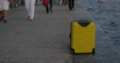 Suitcase on wheels stands on promenade Stock Footage