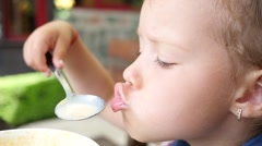 Little cute child girl portrait funny eating soup from spoon closeup slow motion - stock footage