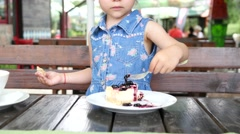 Little child girl eating with fork a sweet tasty cake with jam in restaurant  - stock footage