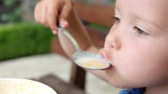 Little cute child girl portrait funny eating a soup from spoon in restaurant  Stock Footage