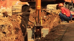 Yellow excavator at building site Stock Footage