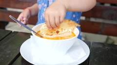 Cute little kid girl eating a pita bread with cheese dip dunk it in soup Stock Footage