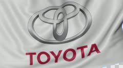 Close up of waving flag with Toyota logo, seamless loop, blue background Stock Footage