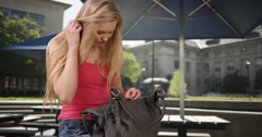Hot young blond looking through her purse for cell phone device Stock Footage