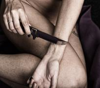 Suicide attempt of a hand cutting a wrist with a knife. Focus on hand - stock photo