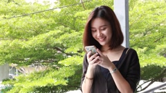 Portrait of thai adult student university beautiful girl using her smart phone Stock Footage