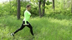 Young woman exercising doing crouch with dumbbels in park Stock Footage