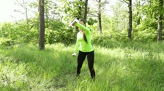 Young woman exercising with dumbbels in park near forest Stock Footage