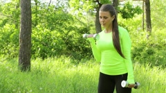 Portrait of pretty young girl doing exercise with dumbbell outdoors - stock footage