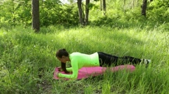 Young woman doing plank exercise on mat in park look at camera smiling Stock Footage