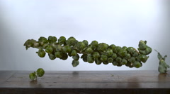 Brussels Sprouts falling in slow motion onto a cutting board Stock Footage