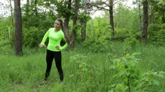 Beautiful young woman doing exercise in park summer day Stock Footage