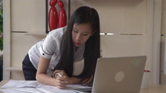 Portrait asian woman designer stands near the desk with architectural sketch Stock Footage
