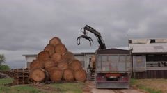 Truck with manipulator unloads haystacks on the ground in farm in 4k UHD video. - stock footage