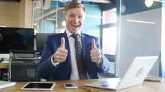 Happy bussinessman giving thumbs up to camera in his office Stock Footage