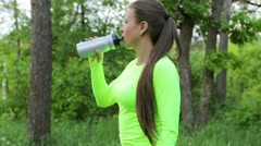 Woman drink water after sport forest look at camera and smiling show tumbs up - stock footage