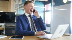 Successful young  businessman talking on smart phone  in office Stock Footage